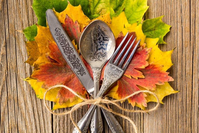 Herbstabendessengedeck für Erntedankfest mit bunten Ahornblättern auf rustikalen hölzernen Brettern stockfotografie