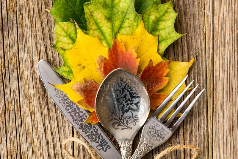 Herbstabendessengedeck für Erntedankfest mit bunten Ahornblättern auf rustikalen hölzernen Brettern lizenzfreies stockbild