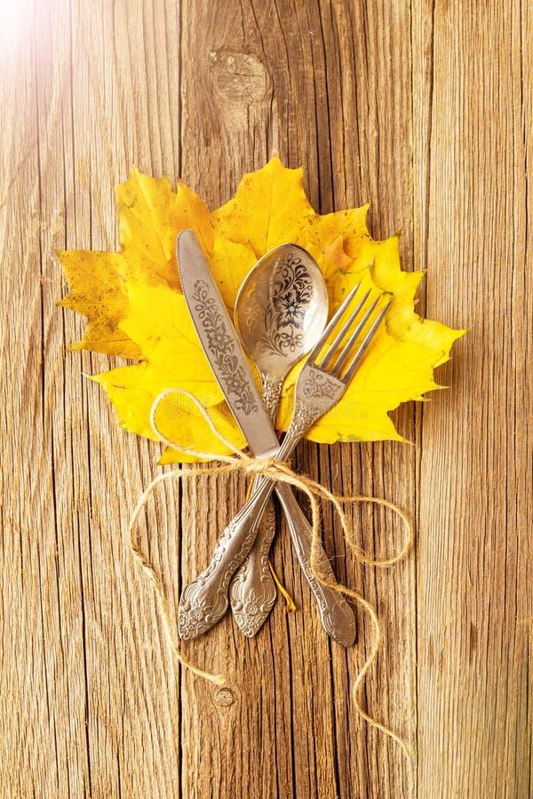 Herbstabendessengedeck für Erntedankfest mit bunten Ahornblättern auf rustikalen hölzernen Brettern lizenzfreie stockbilder