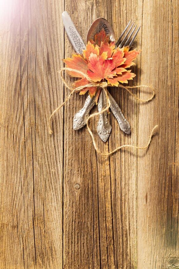 Herbstabendessengedeck für Erntedankfest mit bunten Ahornblättern auf rustikalen hölzernen Brettern stockbild