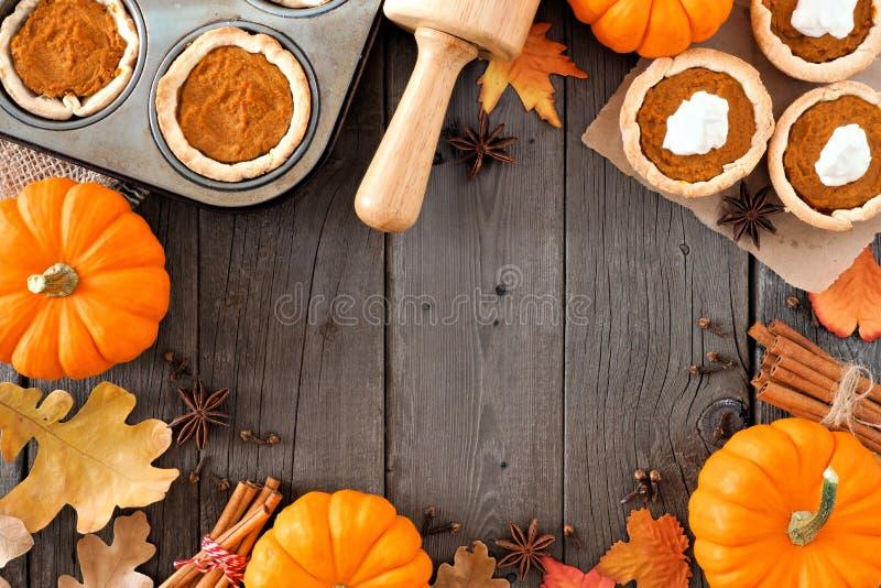 Herbstbackenrahmen mit Kürbiskuchentörtchen über Holz lizenzfreies stockfoto