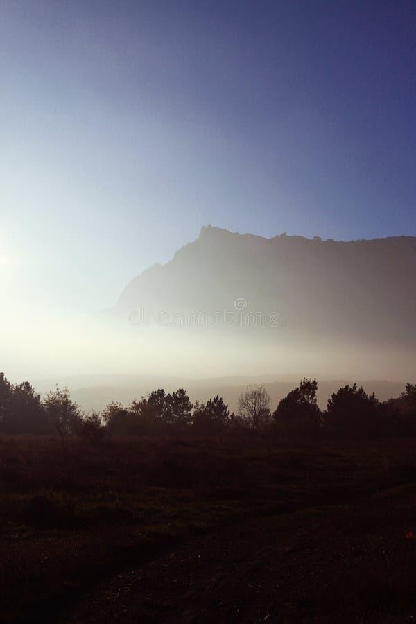 Herbstberge im Nebel und in der kurvenreichen Straße Sonnenuntergang stockfotos
