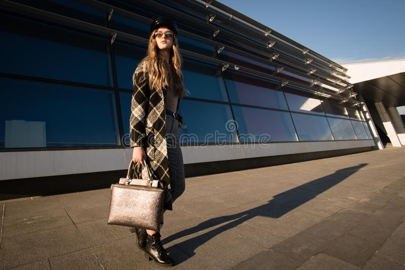 Herbstbild einer jungen Frau auf der Straße Frau in einem modernen Mantel und in einer Handtasche stockfoto