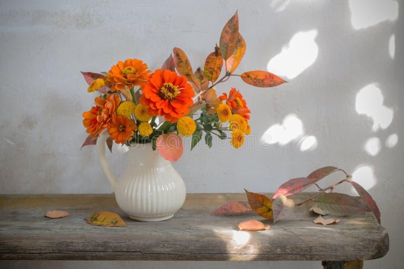 Herbstblumen im Pitcher auf Holzbank lizenzfreies stockfoto