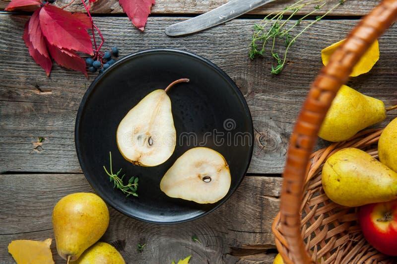 Herbsterntekonzept - schneiden Sie frische reife Birne auf dem Schwarzblech und der Gruppe von gelben Birnen im Korb und auf dem  stockfotos
