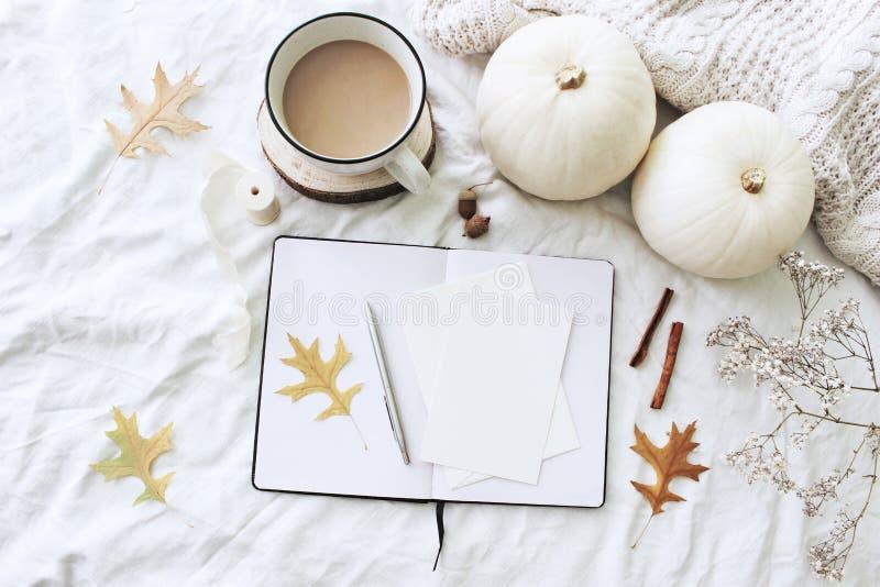 Herbstfrühstück in der Bettzusammensetzung Leere Karten, Notizbuchmodell Tasse Kaffee, weiße Kürbise, Strickjacke, Eiche verlässt lizenzfreie stockbilder