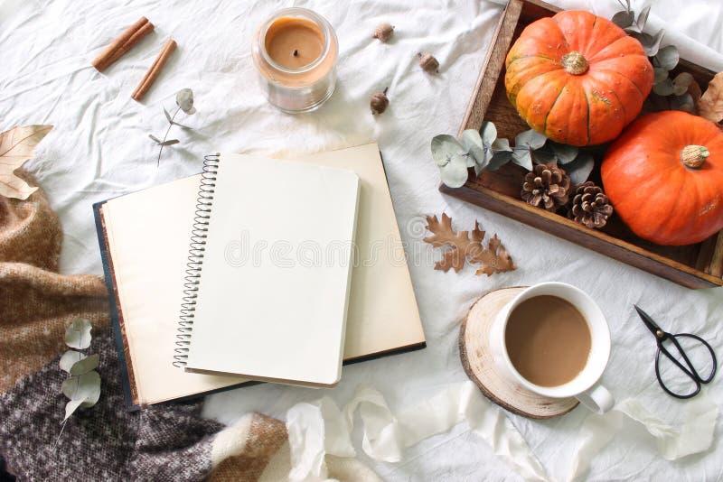 Herbstfrühstück in der Bettzusammensetzung Leerer Notizblock, Buchmodell Kaffee, Kerze, Eukalyptusblätter und Kürbise auf hölzern stockfotografie