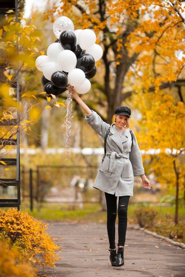 Herbstfrau im Herbstpark mit Ballonen Modemädchen im grauen Mantel lizenzfreies stockfoto