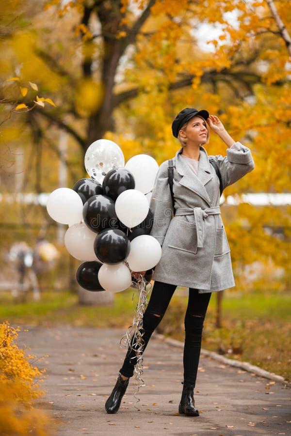 Herbstfrau im Herbstpark mit Ballonen Modemädchen im grauen Mantel stockfotografie