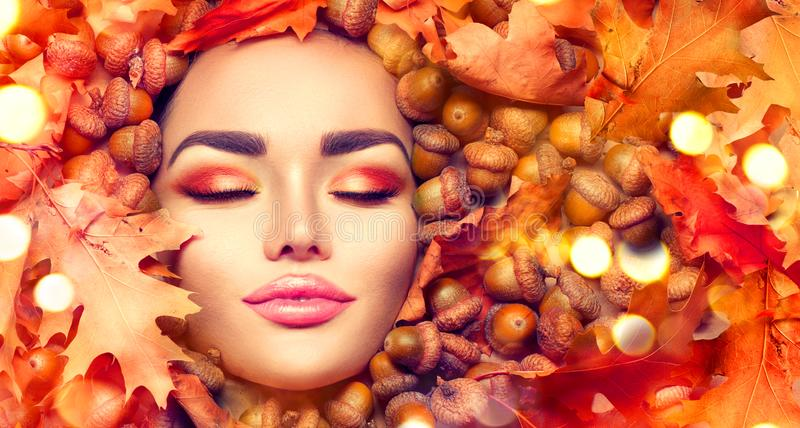 Herbstfrauenmake-up Schönes Herbstmodell-Mädchenporträt mit hellen gelben, roten und orange Farbblättern und den Eicheneicheln lizenzfreie stockfotos