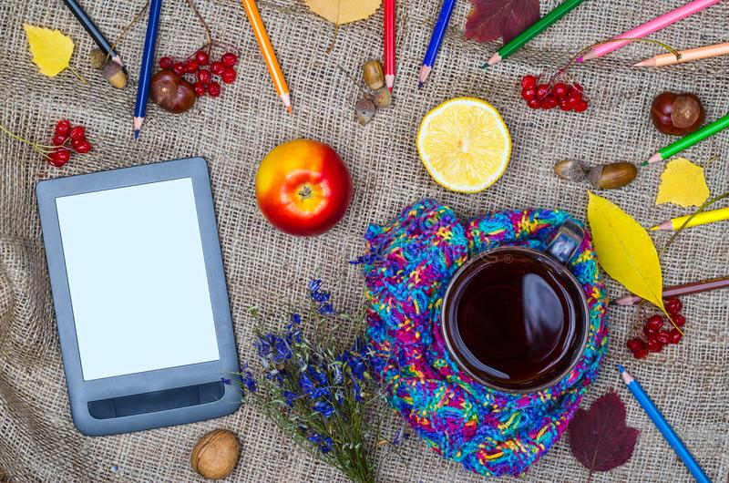 Herbsthintergrund: eine Tablette, eine Tasse Tee und farbiges cardashi t lizenzfreies stockbild