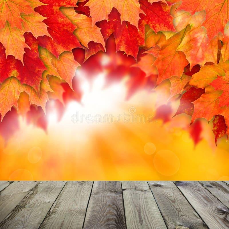 Herbsthintergrund mit Bl?ttern Bunte Fallblätter und abstraktes Gold-bokeh Licht mit leerem dunklem Hintergrund des hölzernen Bre stockbild