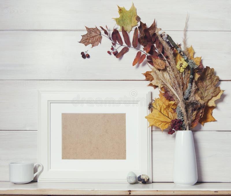 Herbsthintergrundschablone mit weißem Holzrahmen und trocknen Urlaub stockbild