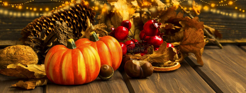 Herbstkürbise mit festlichen Lichtern und Dekorationen auf hölzernem Ba stockfoto