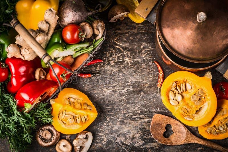 Herbstkürbisteller, der Vorbereitung mit dem Kochen des Topfes, des Gemüses und der Pilze auf rustikalem hölzernem Hintergrund, D lizenzfreie stockfotografie