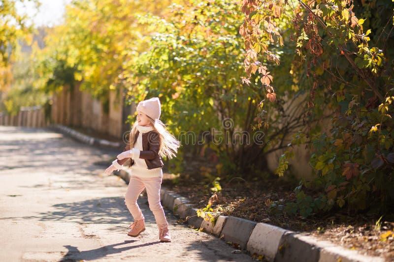 Herbstkind-` s Mode Ein kleines Mädchen tanzt, springt und freut sich im Fall gegen einen Hintergrund des gelben und roten Laubs  lizenzfreies stockfoto