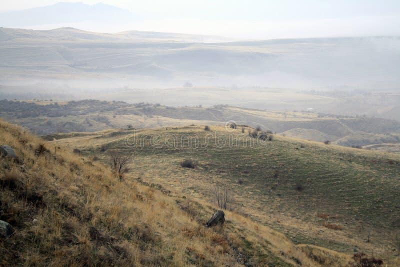 Herbstlandschaft, Felder und Wiesen, Schnee-mit einer Kappe bedeckte Berge und Hügel von Armenien stockfotografie