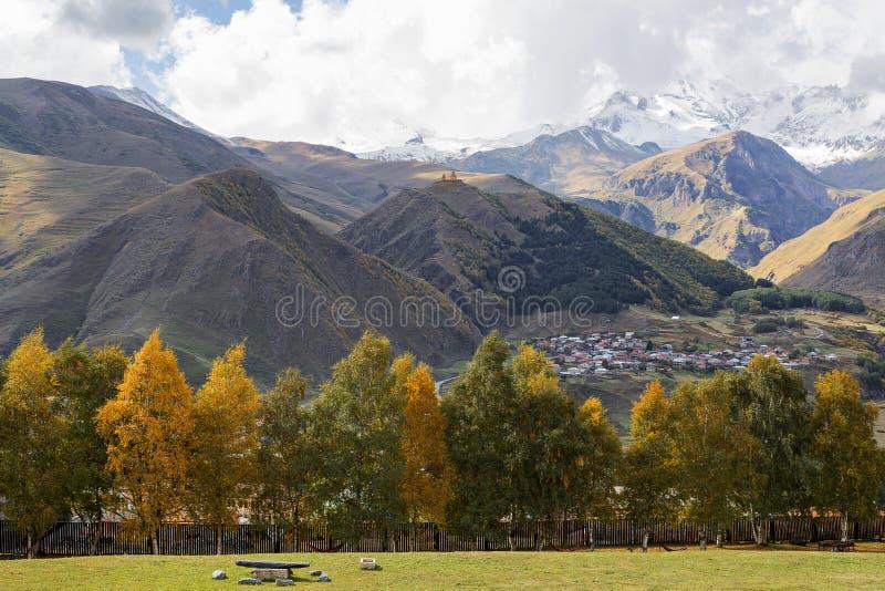 Herbstlaub und Berglandschaft in Georgia, Kaukasus mit Gergeti-Kirche auf die Oberseite des Berges lizenzfreie stockfotos