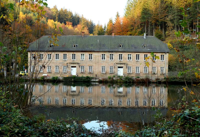Herbstlaub und ein Gebäude reflektiert im Wasser stockbilder
