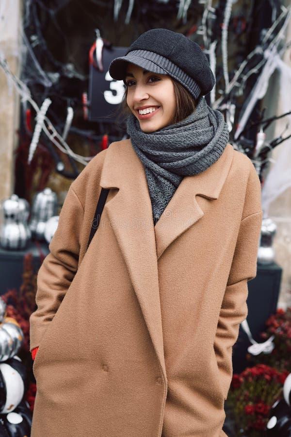 Herbstlebensstilporträt der schönen lächelnden Frau im beige Mantel, im warmen Schal und im Hut auf der Straße mit Halloween lizenzfreie stockfotos