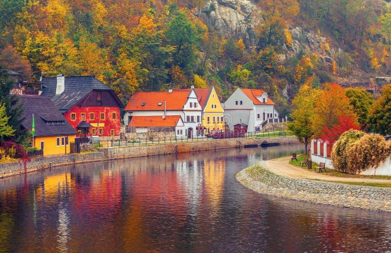 Herbstliche Landschaft mit farbigem Haus über Fluss lizenzfreie stockbilder