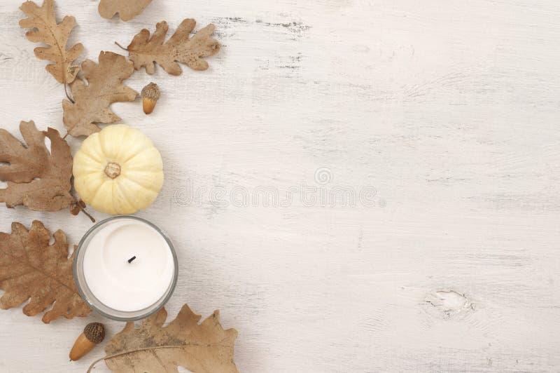 Herbstliches Stillleben mit Eichenblättern, -eicheln, -kürbis und -kerze lizenzfreie stockfotos