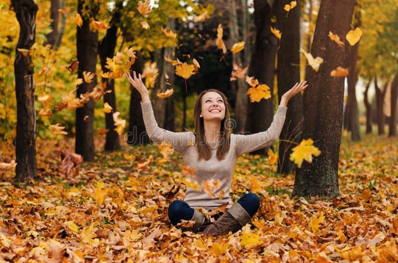 Herbstmädchen, das im Stadtpark spielt Fallfrauenporträt der glücklichen reizenden und schönen jungen Frau im Wald in den Fallfar lizenzfreie stockbilder