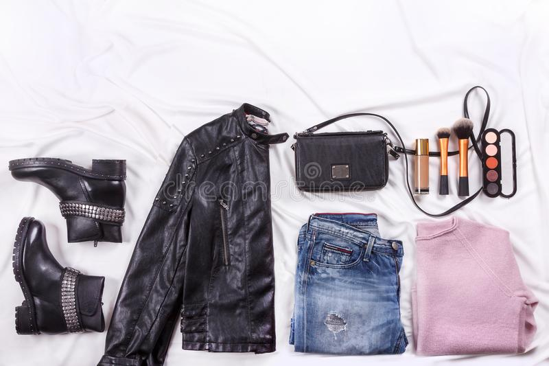 Herbstmode Blogger ` s Ausstattung Rosa Wolle strickte Wolljacke, Blue Jeans vom Denim, schwarze Tasche und kosmetische brushs lizenzfreie stockfotos