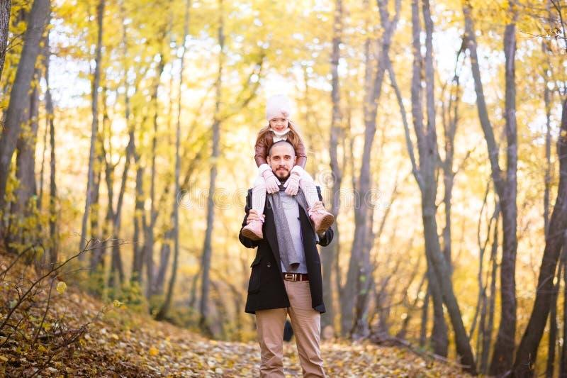 Herbstmode für Kinder und die ganze Familie Eine kleine Tochter sitzt auf den Schultern des Vaters im Hals gegen das BAC lizenzfreies stockbild