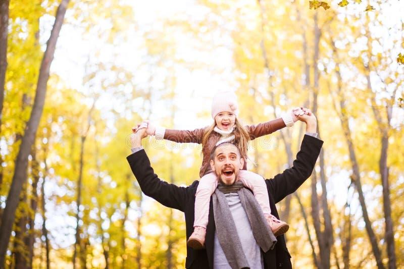 Herbstmode für Kinder und die ganze Familie Eine kleine Tochter sitzt auf den Schultern des Vaters im Hals gegen das BAC stockfotografie