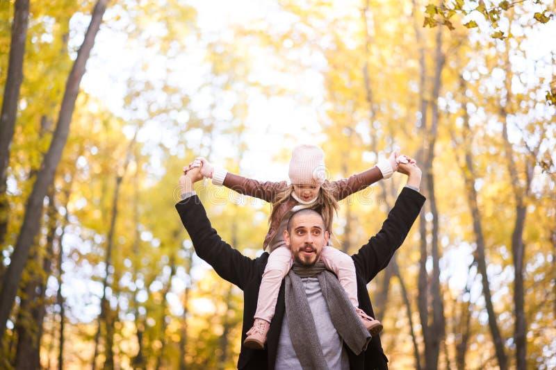 Herbstmode für Kinder und die ganze Familie Eine kleine Tochter sitzt auf den Schultern des Vaters im Hals gegen das BAC stockbild