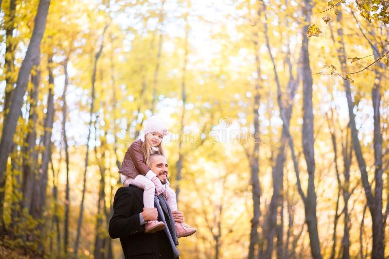 Herbstmode für Kinder und die ganze Familie Eine kleine Tochter sitzt auf den Schultern des Vaters im Hals gegen das BAC lizenzfreie stockbilder