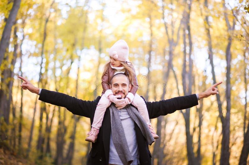 Herbstmode für Kinder und die ganze Familie Eine kleine Tochter sitzt auf den Schultern des Vaters im Hals gegen das BAC stockfoto