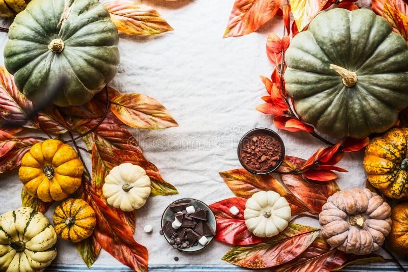 Herbstnahrungsmittelhintergrund mit bunten Kürbisen, Schokolade, Gewürzen, Nüssen und Herbstlaub, Draufsicht Herbststillleben mit stockfotos