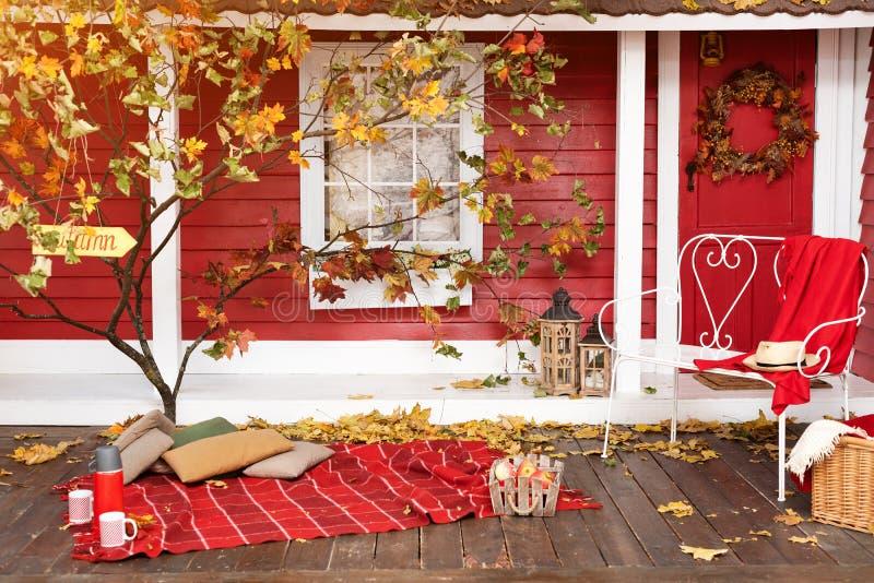 Herbstpicknick auf der Terrasse Rotes Plaid, Korb mit Äpfeln und Thermosflasche mit heißem Getränk Veranda des Landschaftshauses  lizenzfreie stockfotografie