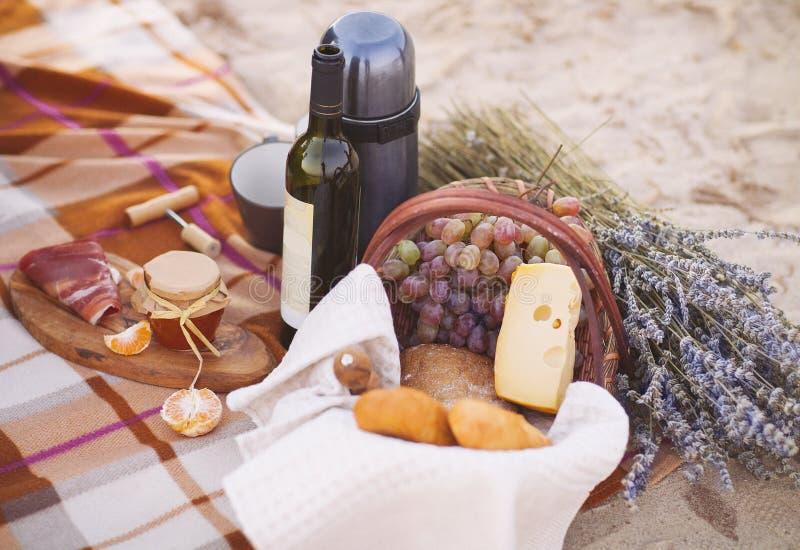 Herbstpicknick durch das Meer mit Wein, Trauben, Brot und Käse lizenzfreie stockbilder