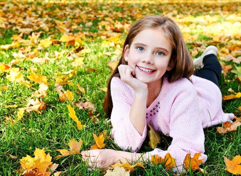 Herbstporträt des entzückenden lächelnden Kindes des kleinen Mädchens, das auf Gras mit Blättern liegt lizenzfreie stockfotos