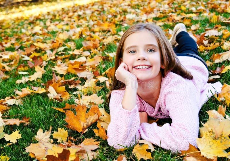 Herbstporträt des entzückenden lächelnden Kindes des kleinen Mädchens, das auf Gras mit Blättern liegt lizenzfreie stockbilder