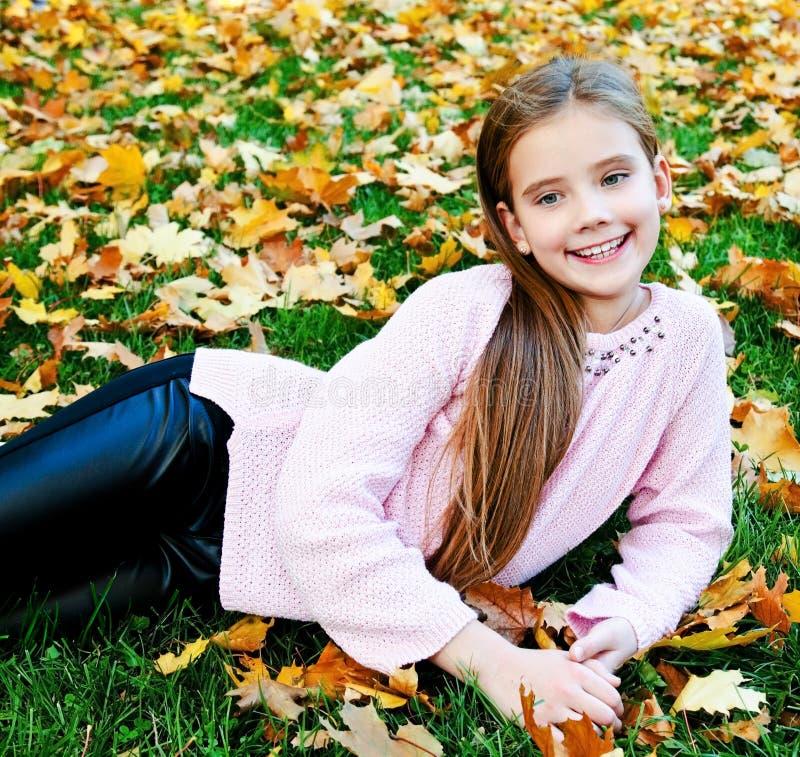 Herbstporträt des entzückenden lächelnden Kindes des kleinen Mädchens, das auf Gras mit Blättern liegt lizenzfreies stockbild