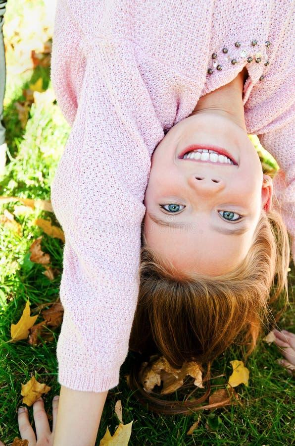 Herbstporträt des entzückenden lächelnden Kindes des kleinen Mädchens, das auf Gras umgedreht steht und Spaß hat stockbilder