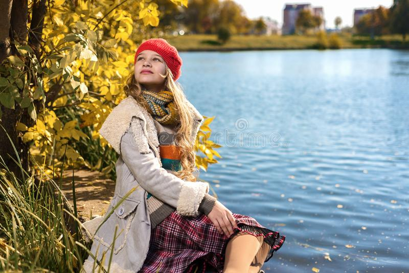 Herbstporträt des jungen hübschen Mädchens im roten Hut lizenzfreie stockbilder