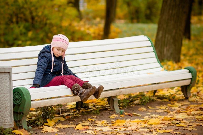 Herbstporträt des traurigen einsamen Kindermädchens, das auf Bank im Park im warmen blauen Mantel und im Hut, herein genießend We lizenzfreie stockbilder
