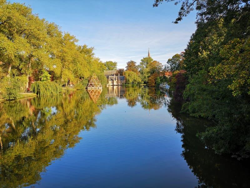 Herbstreflexionen in einem See in Brügge stockbild