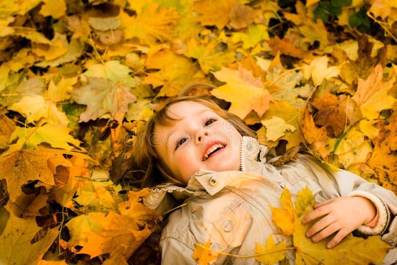 Herbstsaison - Kind in gefallenen Blättern stockfoto