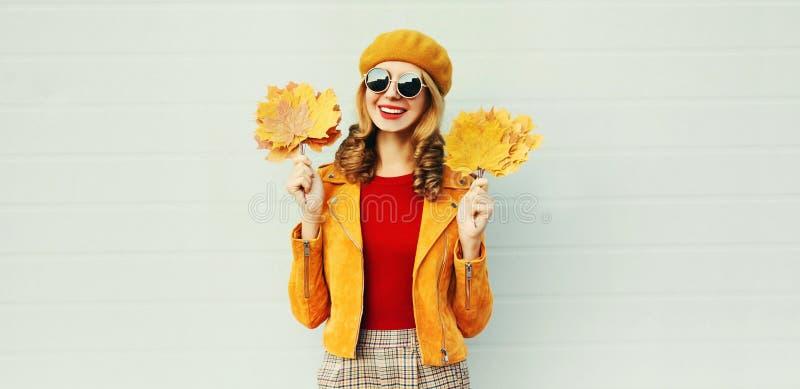 Herbstsaison! Stilvolle glückliche lächelnde Frau mit gelben Ahornblättern im französischen Barett, das über grauer Wand aufwirft stockfoto