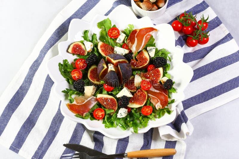Herbstsalat mit Tomaten der Feigen, des Arugulablattes, des Blauschimmelkäses Dorblu, des Prosciutto und der Kirsche Flache Lage  lizenzfreies stockbild