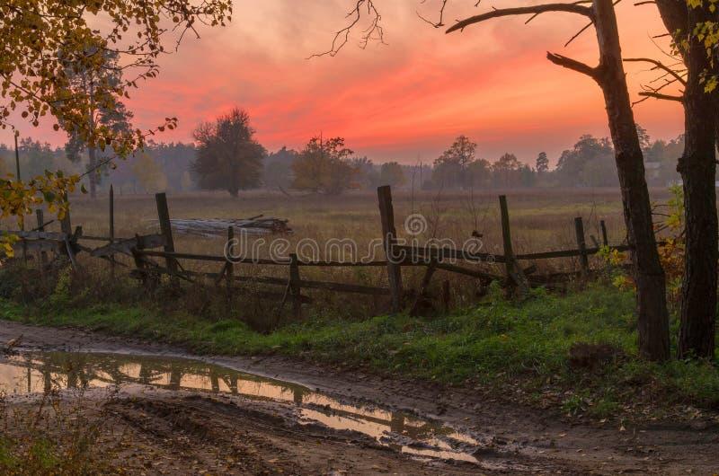 Herbstsonnenuntergang in der Landschaft Abendherbstlandschaft mit einem alten Zaun lizenzfreie stockfotografie