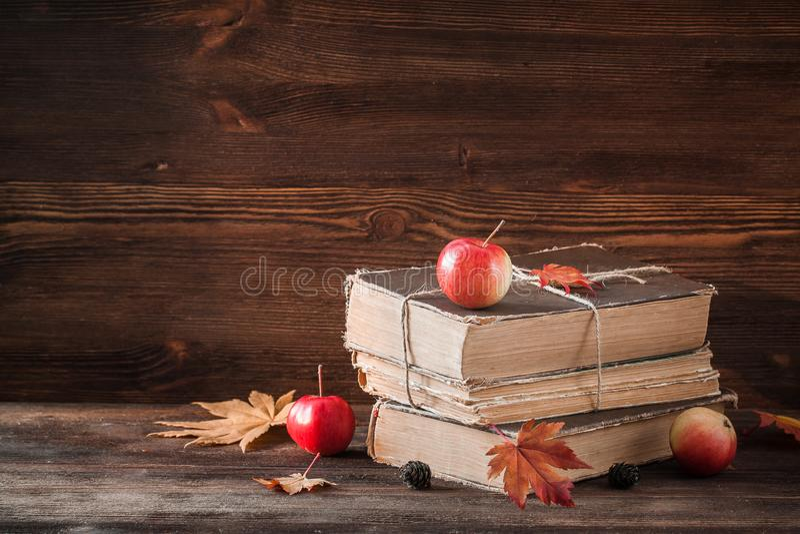Herbststillleben mit alten Büchern, Äpfel, Ahornblätter auf dem hölzernen Hintergrund stockfotografie