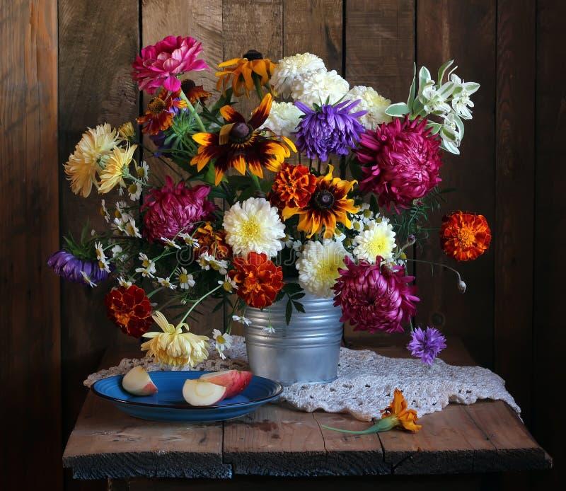 Herbststillleben mit Blumen und Apple bessert auf der Platte aus stockfotografie