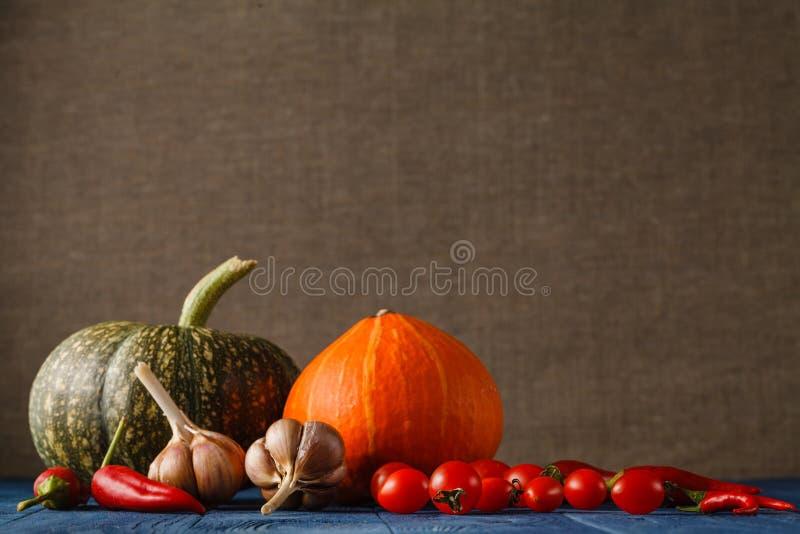 Herbststillleben mit Kürbisen und Blättern auf altem hölzernem backgro stockfotografie